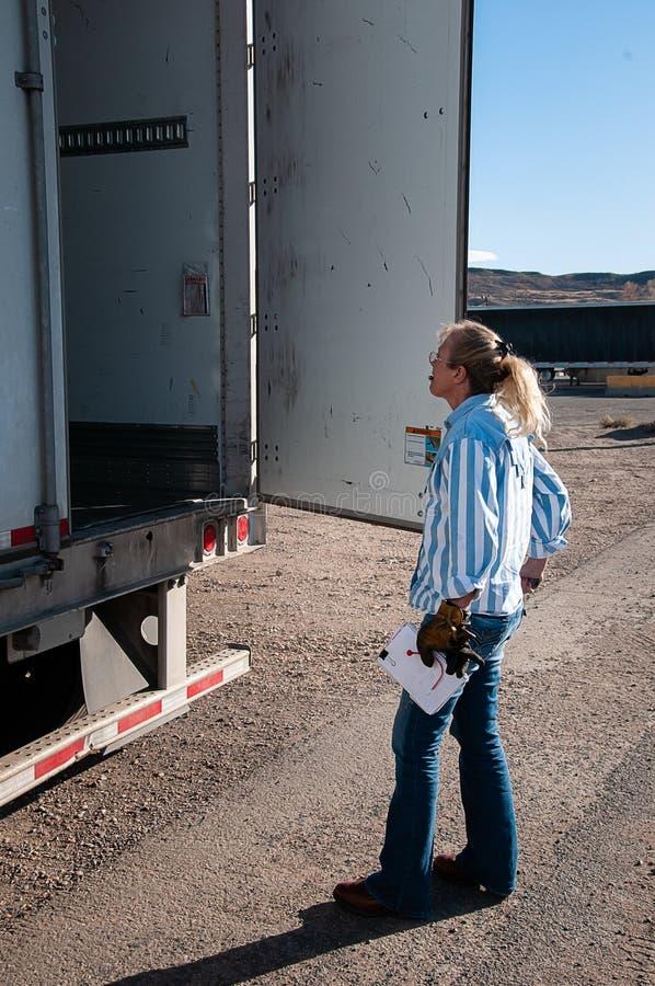 Autista di camion della donna che ispeziona il contenuto del suo rimorchio caricato fotografia stock libera da diritti