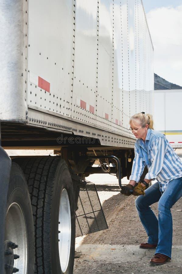 Autista di camion della donna che solleva i piedini del rimorchio immagini stock