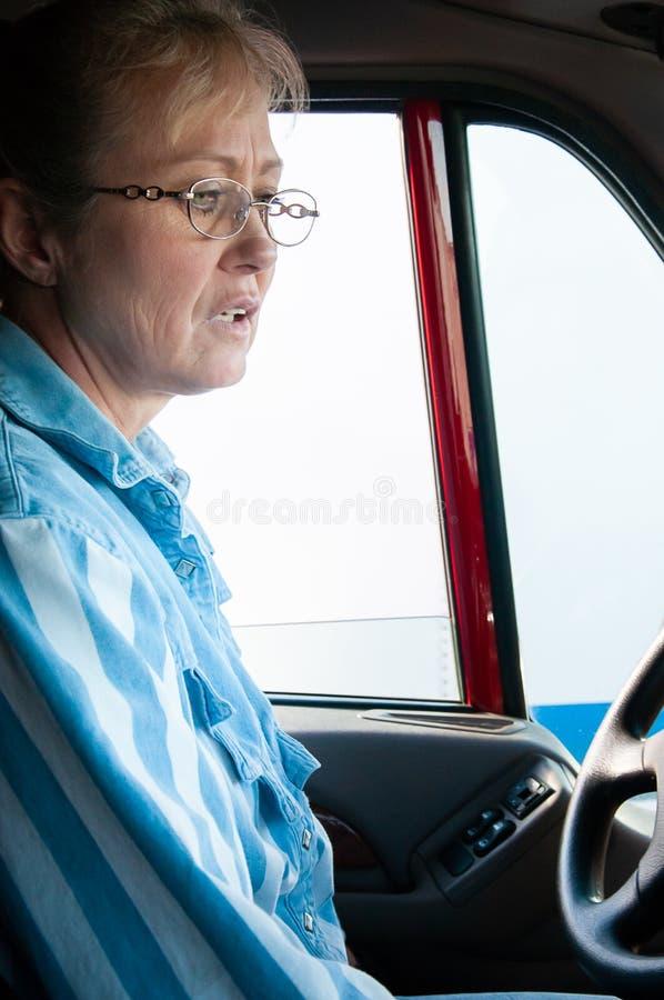Autista di camion della donna dentro la carrozza di un semi-camion immagini stock libere da diritti