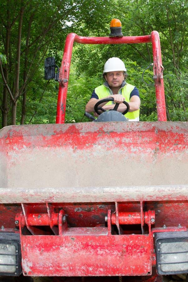 autista di camion dello scarico su un sito della costruzione di edifici fotografia stock