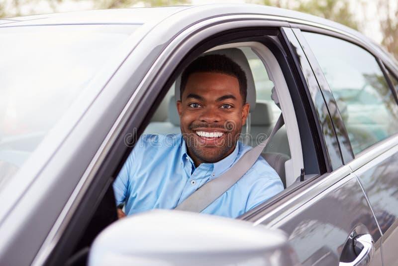 Autista maschio afroamericano che guarda alla macchina fotografica attraverso la finestra di automobile fotografie stock