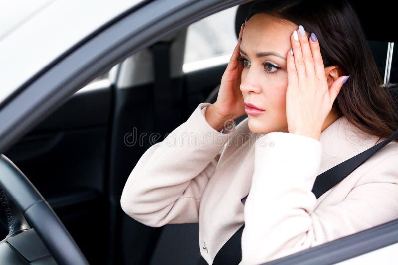 Autista sollecitato della giovane donna in un'automobile immagini stock
