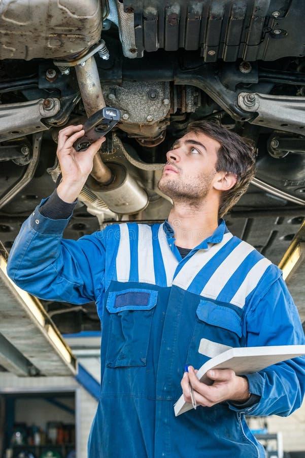 AUTO-Abgasanlage Mechaniker-Holding Flashlight Whiles Untersuchungs lizenzfreies stockfoto