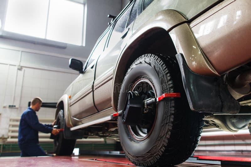 Auto alinhamento de roda na garagem, manutenção de SUV imagem de stock
