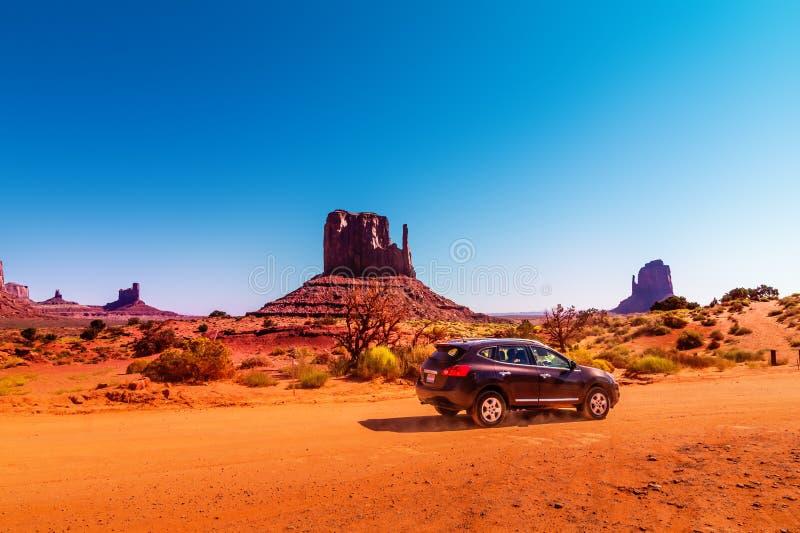Auto auf dem Monument-Tal-Antrieb Der Tal-Antrieb ist ein szenischer Schotterweg durch Navajo-Stammes- Park zwischen Arizona und  lizenzfreie stockbilder