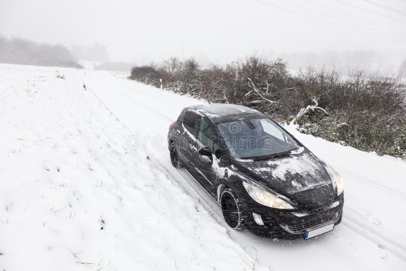 Auto auf einem Schnee bedeckte Straße lizenzfreie stockbilder