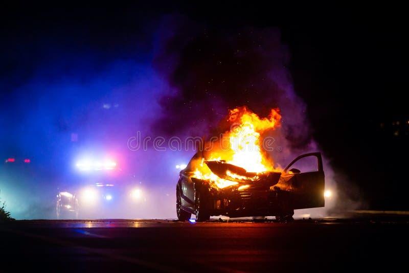 Auto auf Feuer nachts mit Polizei beleuchtet im Hintergrund lizenzfreies stockbild