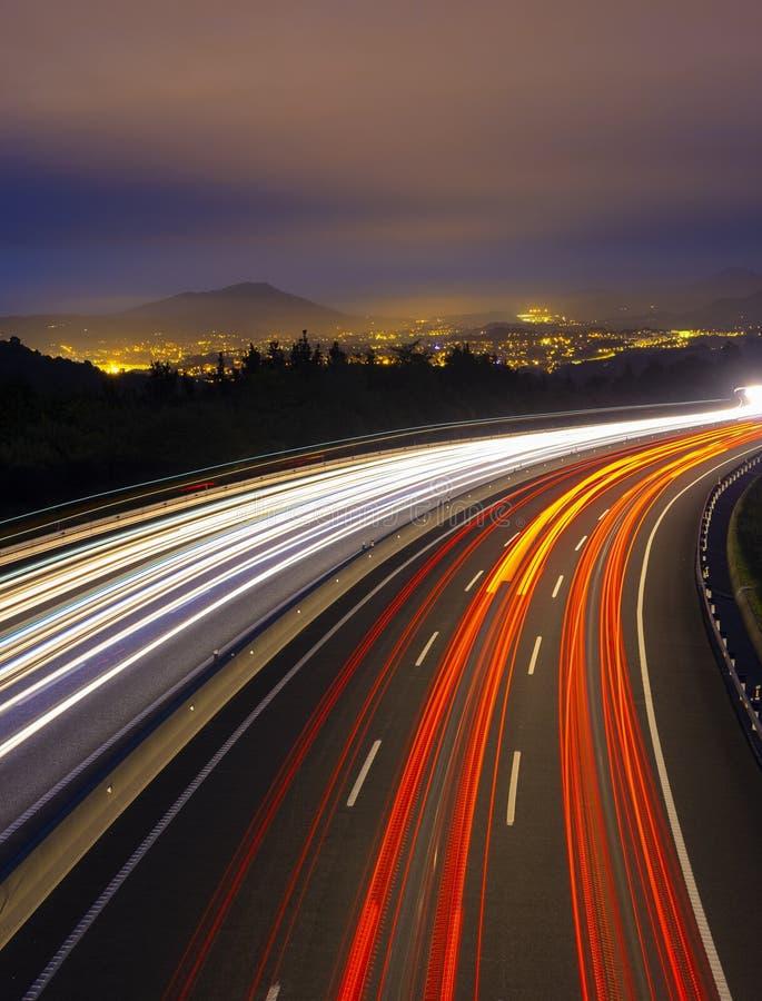 Auto beleuchtet auf der Autobahn in Richtung der Stadt lizenzfreie stockfotos