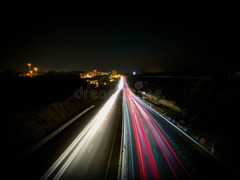 Auto beleuchtet auf einer Landstra?e und einem Freileitungsmast nachts, langes Belichtungsfoto des Verkehrs lizenzfreie stockfotografie