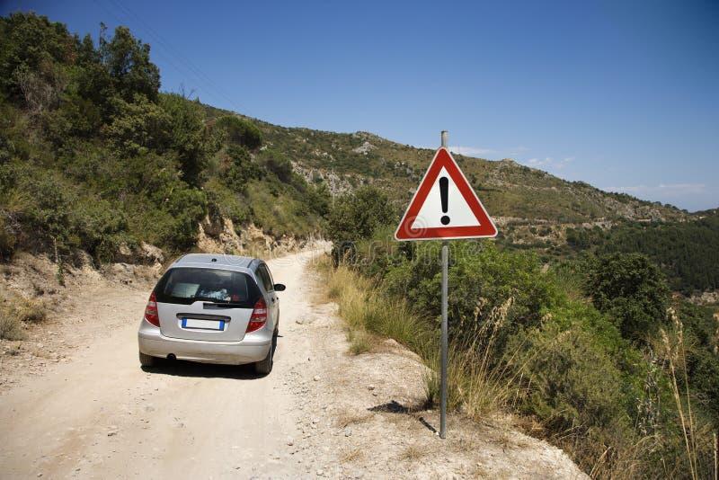 Auto bij de landweg met voorzichtigheidsteken. stock foto's