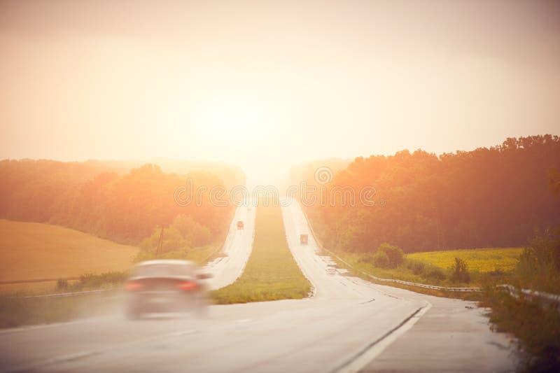 Auto bij hoge snelheid op de weg bij zonsopgang royalty-vrije stock afbeelding