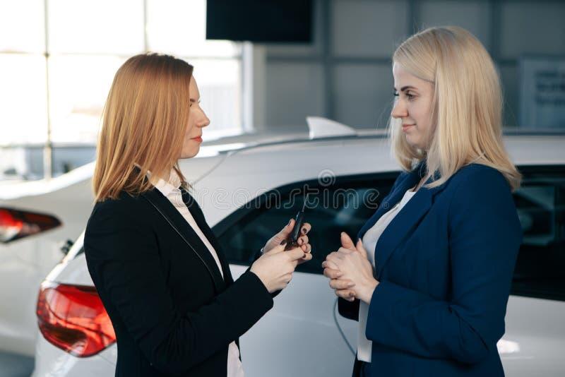 Auto biznes, samochodowa sprzedaż, konsumeryzm i ludzie pojęć, - szczęśliwa kobieta z samochodowym handlowem w auto przedstawieni obrazy stock