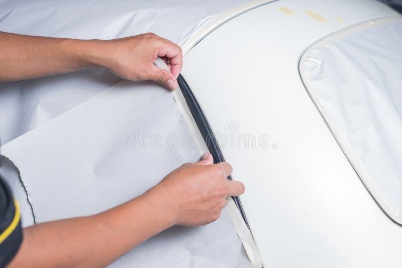 Auto body repair series. Closeup of worker's hand masking car stock image