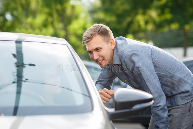 Auto business, car sale, consumerism and people concept - happy couple buying car in auto show or salon royalty free stock image