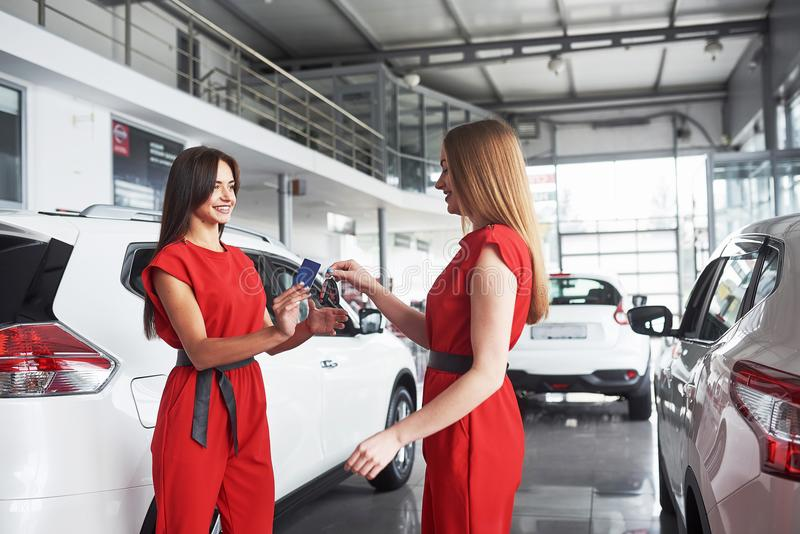 Auto business, car sale, deal, gesture and people concept - close up of dealer giving key to new owner in auto show or stock photo