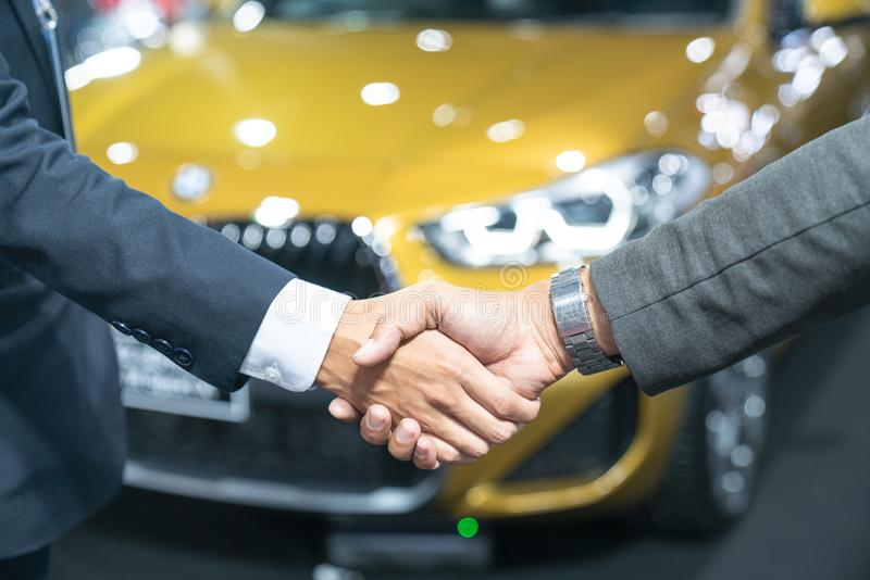 Auto business, car sale, deal, gesture and people concept -new o. Wner and shaking hands in auto show or salon 1 stock photo