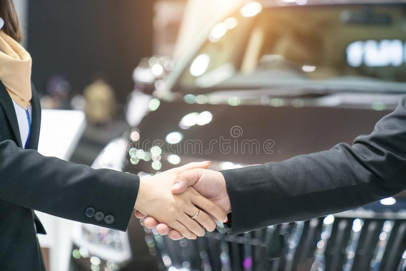 Auto business, car sale, deal, gesture and people concept new ow. Ner and shaking hands in auto show or salon 1 stock photos