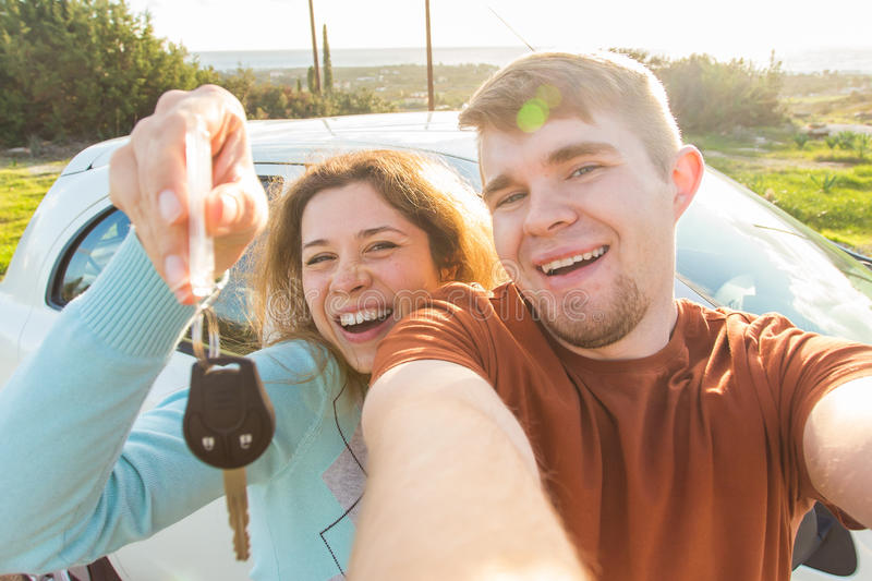 Auto business, car sale, deal and people concept - Happy funny beautiful couple shows key with new car on background royalty free stock image