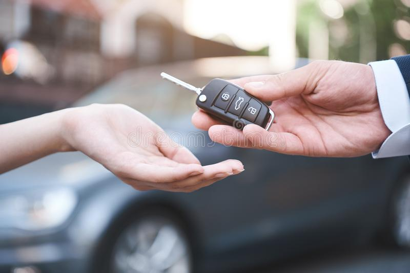 Auto business, car sale, transportation, people and ownership co. Ncept - close up of car salesman giving key to new owner or customer over auto show background royalty free stock image