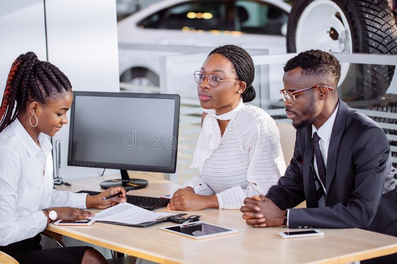 Happy african couple with dealer buying car in auto show or salon. Auto business, sale and people concept - happy african couple with dealer buying car in auto royalty free stock image