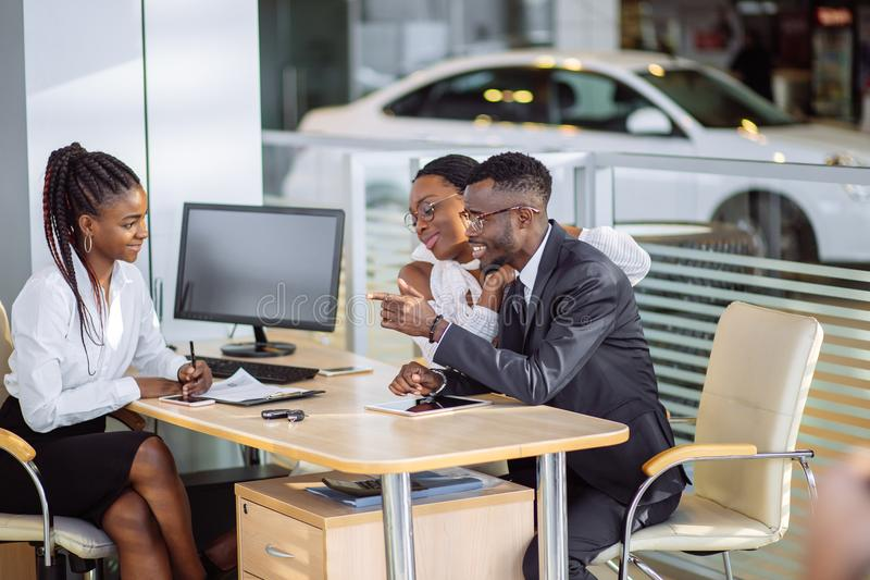 Happy african couple with dealer buying car in auto show or salon. Auto business, sale and people concept - happy african couple with dealer buying car in auto royalty free stock photography