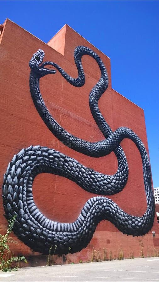 Auto che inghiotte il serpente della parete immagine stock