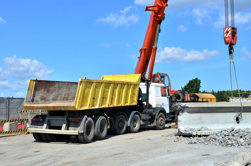 Auto crane loads an old concrete slab into a dump truck at a construction site. stock photography