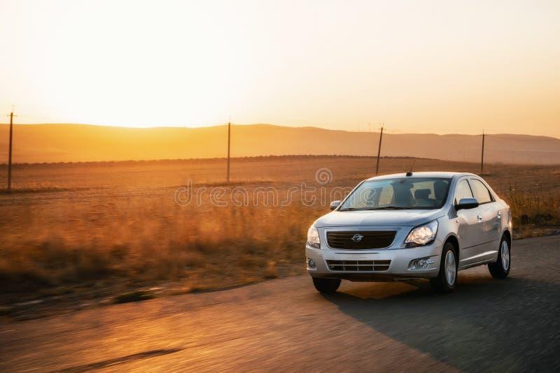 Auto d'argento che guida veloce in campagna via asfalto al tramonto, Uzbekistan immagine stock