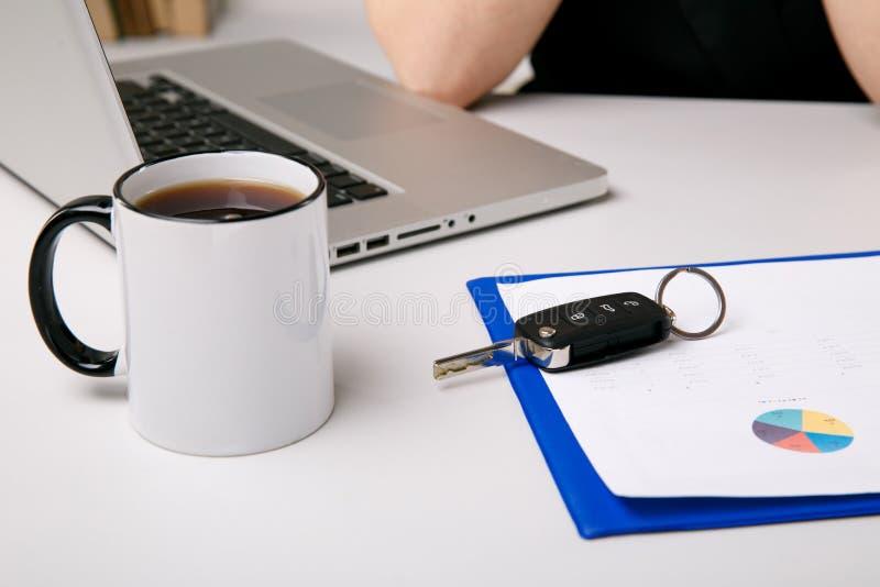 Auto, das Konzept verkauft Dokumente mit Schlüsseln auf dem Schreibtisch Tasse Kaffee und Computer stockbild