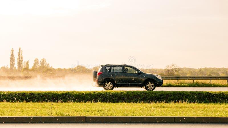 Auto, das schnell auf dem Regnen von Landschaft geht lizenzfreie stockfotos