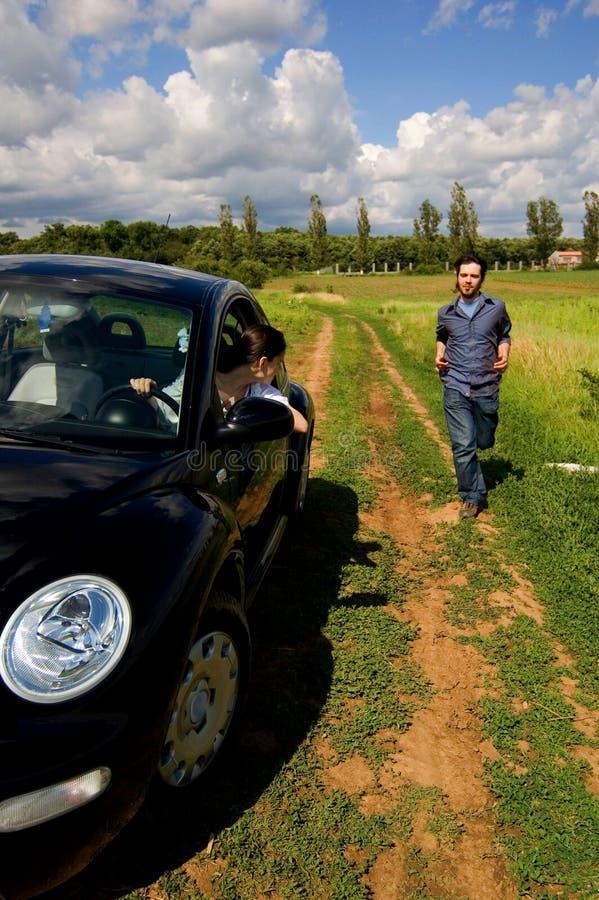 Auto der Mann-nähernden Frau stockfoto