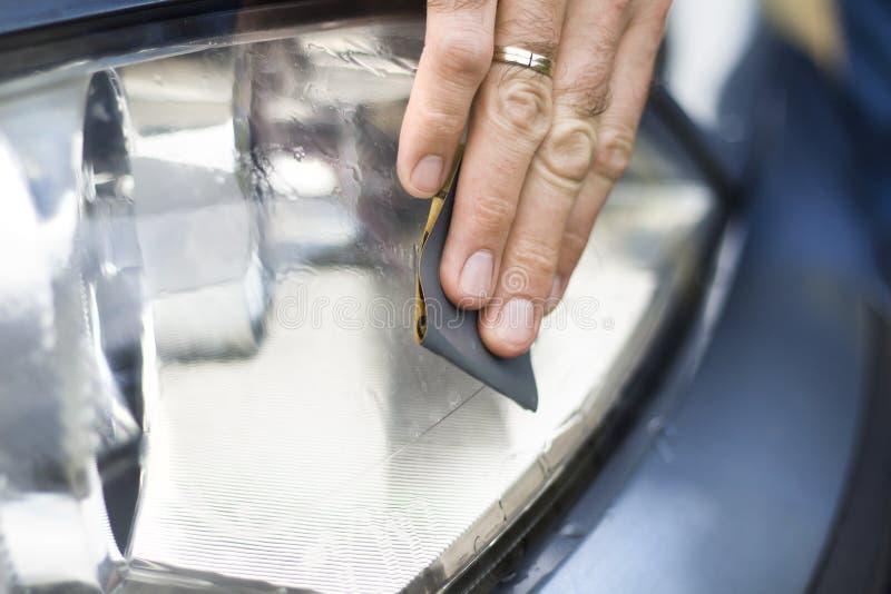 Auto detalhe Renovação do vidro do refletor Polonês com papel abrasivo e água imagens de stock
