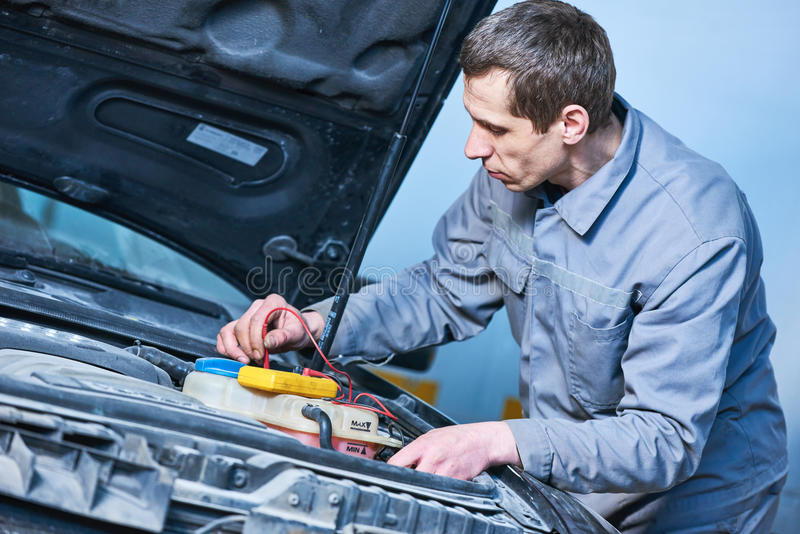 Auto electrician mechanic at work with car royalty free stock image