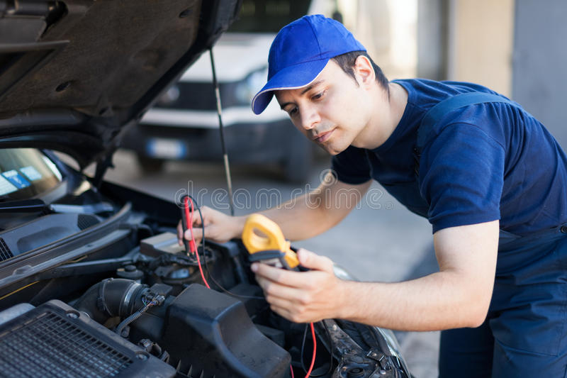 Auto electrician working on a car engine stock images