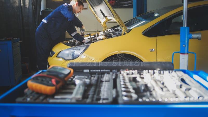 Auto elektronik för bilen - mekaniker reparerar ett bil- skruva av detaljen av bilen - parkera bilen i garage service arkivfoto