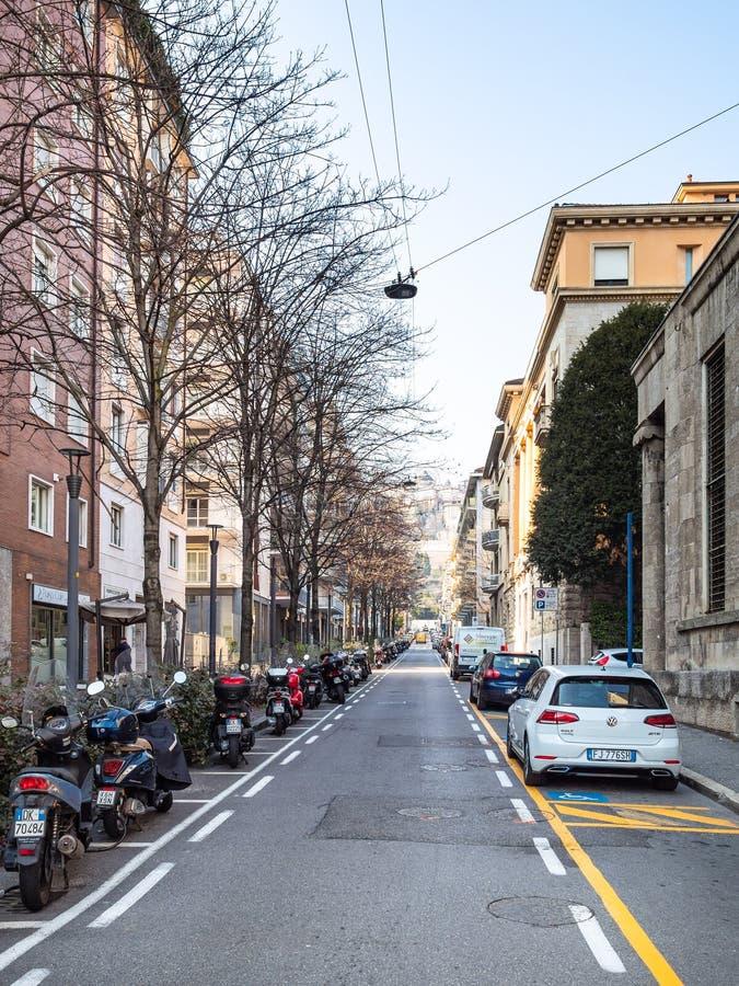 Auto en motorparkeren op straat in Bergamo stock foto