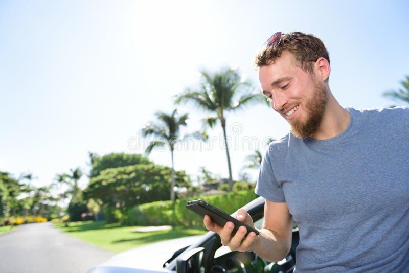 Auto en smartphone app - mens die sms op telefoon texting stock foto