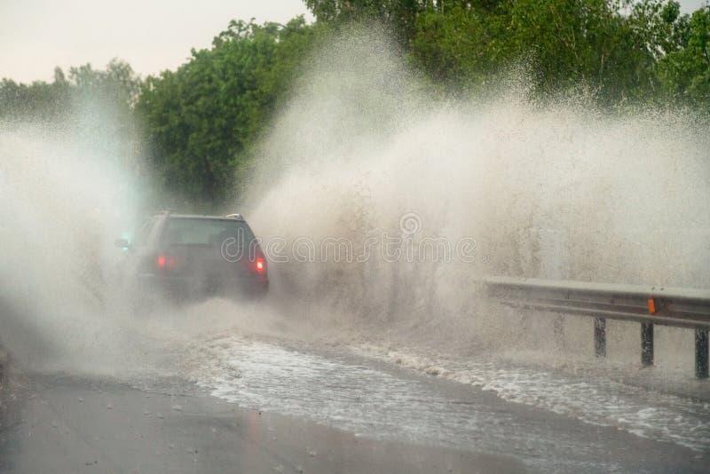Auto f?hrt gegen gro?e Pf?tze am starken Regen, das Wasser, das ?ber dem Auto spritzt Autofahren auf Asphaltstra?e am Gewitter ge stockbilder