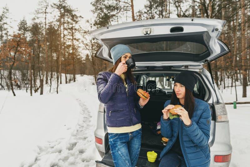 Auto-Gespräches der Freundinwinterabnutzung trinkender Kaffee des schneebedeckten Tageswald lizenzfreie stockfotos