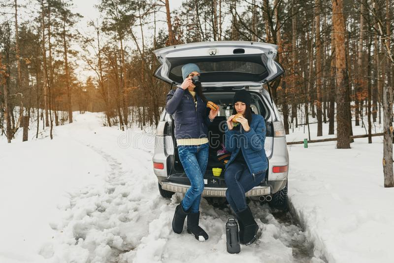 Auto-Gespr?ches der Freundinwinterabnutzung trinkender Kaffee des schneebedeckten Tageswald stockbild
