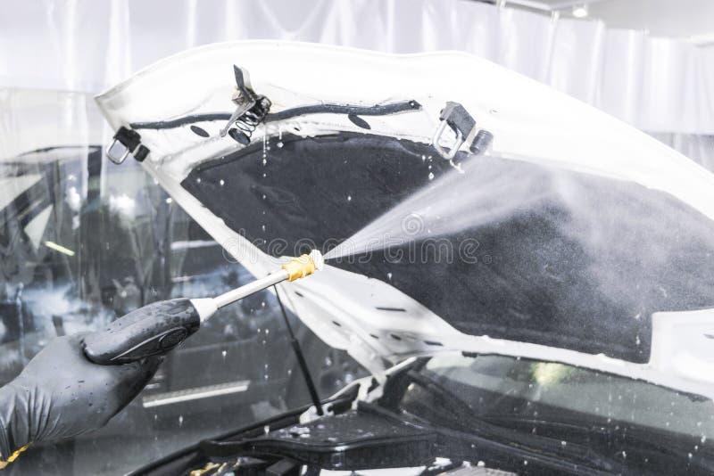 Auto het detailleren Handautowasserettemotor met drukwater Wasmotor van een auto met waterpijp De arbeider van de autowasserettem stock foto