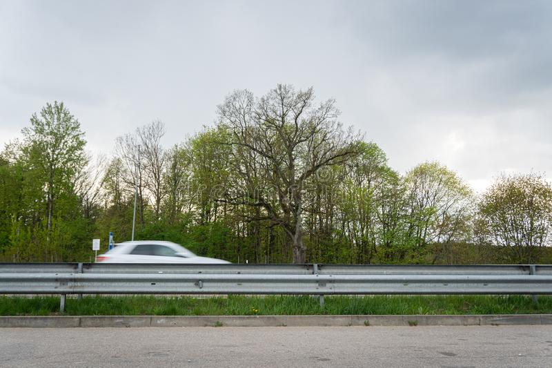 Auto het drijven langs in motieonduidelijk beeld op weg Een mening van weg rustend gebied stock foto
