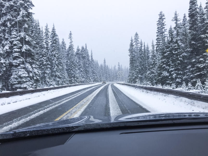 Auto het drijven op snow-covered sneeuwbergweg in de wintersneeuw Het gezichtspunt die van het bestuurders` s standpunt door wind stock afbeeldingen