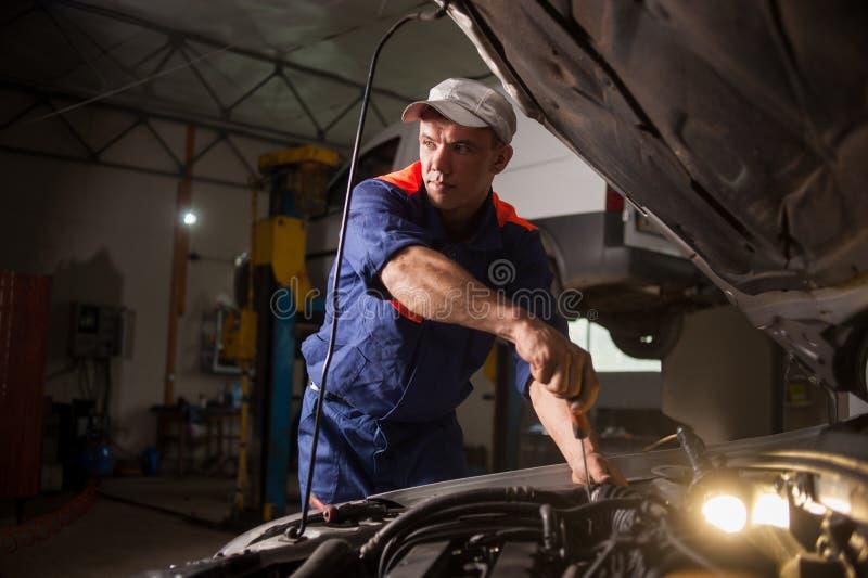 Auto het mechanische werken in de autoreparatiedienst Het herstellen van auto het gebruiken stock afbeelding
