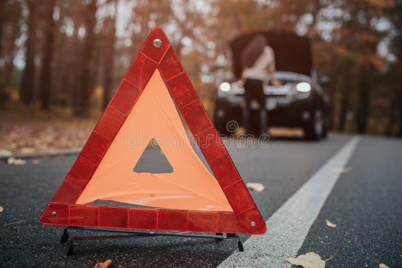 Auto hjälp och försäkring, problem, medan resa begrepp Bruten bil och auto triangel på vägen, vänta på för kvinna arkivfoto
