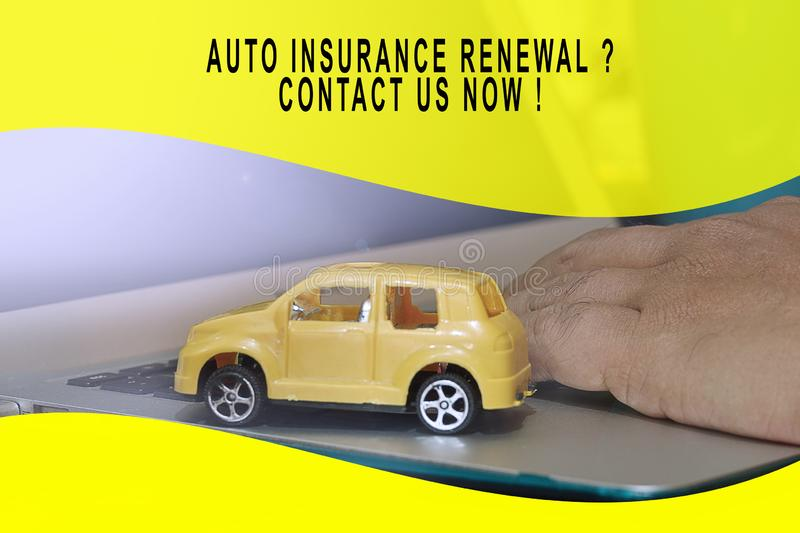 Auto insurance conceptual with small yellow car model on a laptop.  royalty free stock images