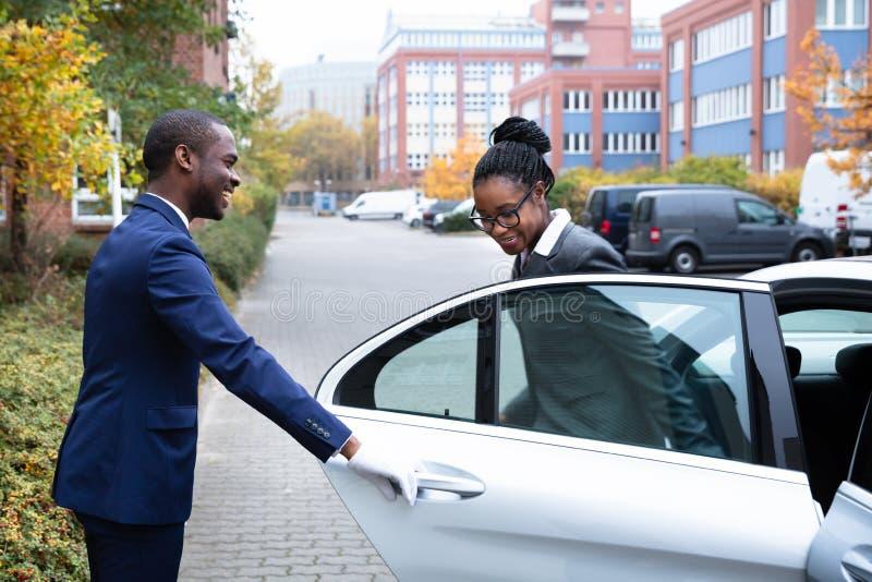 Auto Kammerdiener-Opening Door For-Gesch?ftsfrau-Getting Out Ofs A lizenzfreie stockfotos