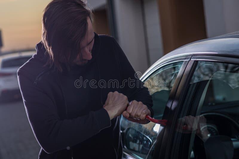 Auto ladrão no passa-montanhas preto que tenta quebrar no carro foto de stock royalty free