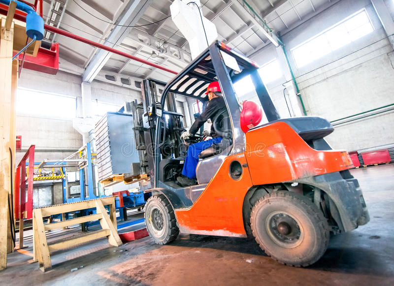 Auto loader with concrete blocks in the warehouse factory. Auto loader with concrete blocks in the bright warehouse factory stock images
