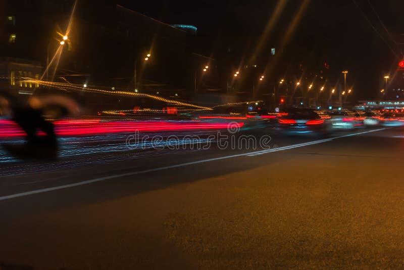 Auto, luces de calle de la ciudad y velocidad El extracto empañó el fondo colorido del tráfico urbano de la noche de la calle con fotografía de archivo
